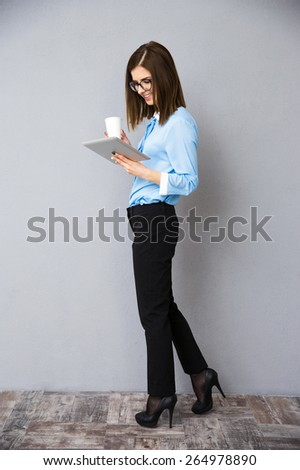 Full length portrait of a businesswoman with cup of coffee and tablet computer. Wearing in black pants and blue shirt. - stock photo