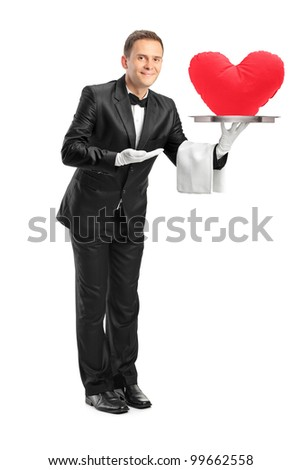 Full length portrait of a butler holding a tray with a red heart shape on it isolated on white background - stock photo