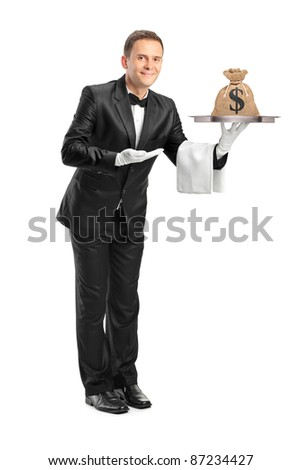 Full length portrait of a butler with bow tie holding a tray with a money bag on it isolated against white background