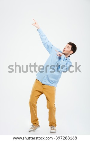 Full length portrait of a casual man pointing fingers on something isolated on a white background