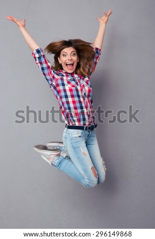 Full length portrait of a casual woman in jeans and shirt jumping over gray background - stock photo