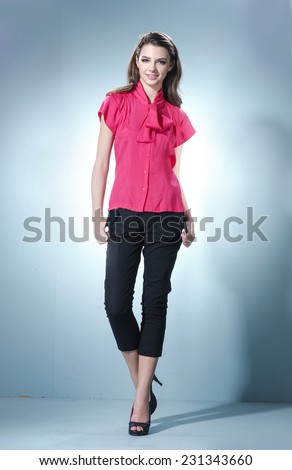 Full length portrait of a casual young fashion model walking in studio - stock photo