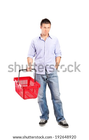 Full length portrait of a casual young man holding an empty shopping basket isolated on white background