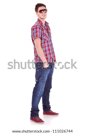 Full length portrait of a casual young man standing with hands in pockets over white background - stock photo