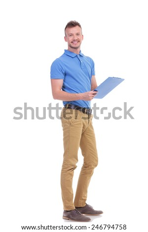 full length portrait of a casual young man taking some notes on a clipboard and smiling for the camera. on a white background - stock photo