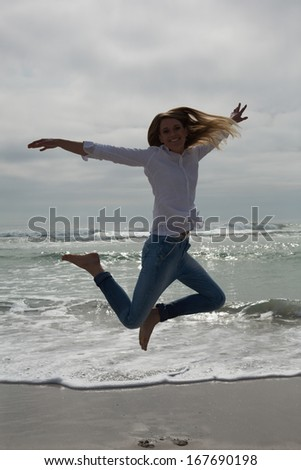 Full length portrait of a casual young woman jumping at the beach
