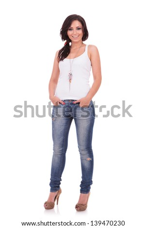 full length portrait of a casual young woman standing with her hands in her pockets and smiling to the camera. on white background