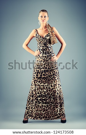 Full length portrait of a charming fashionable woman posing over gray background. - stock photo