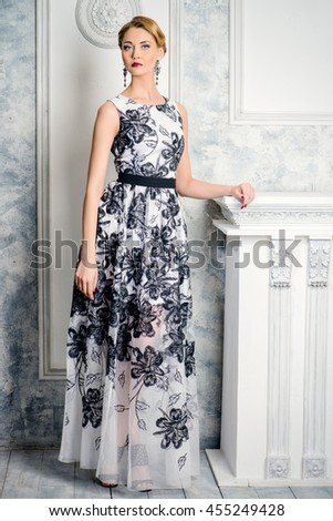 Full length portrait of a charming woman in beautiful evening dress standing by a fireplace in a room with classical vintage interior. Jewellery. Fashion shot. Hairstyle. - stock photo