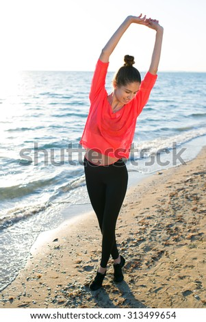 Full length portrait of a charming young fit woman stretching with arms up while standing on the beach in summer sunny day, gorgeous happy female with beautiful figure warm up exercising at seaside  - stock photo
