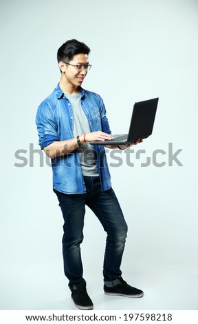 Full length portrait of a cheerful asian man using laptop on gray background - stock photo