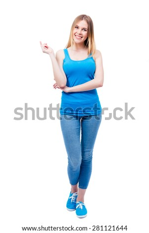 Full length portrait of a cheerful beautiful woman isolated on a white background. Wearing in blue shirt and jeans. Looking at camera - stock photo