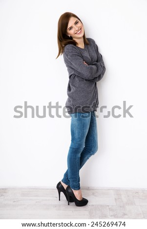 Full length portrait of a cheerful beautiful woman with arms folded - stock photo