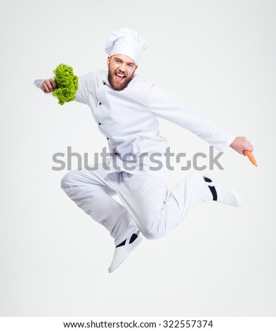 Full length portrait of a cheerful chef cook dancing isolated on a white background - stock photo