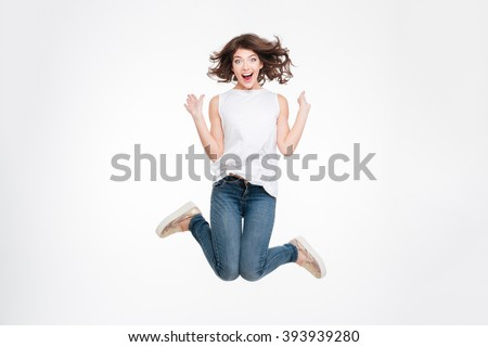 Full length portrait of a cheerful cute woman jumping isolated on a white background - stock photo