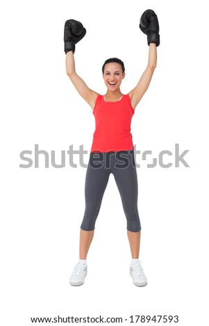 Full length portrait of a cheerful female boxer raising hands over white background
