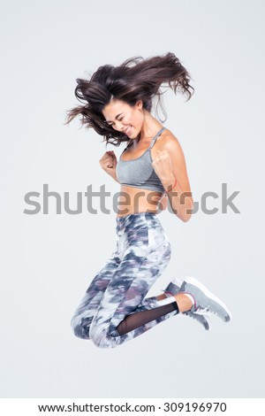 Full length portrait of a cheerful fitness woman jumping isolated on a white background - stock photo