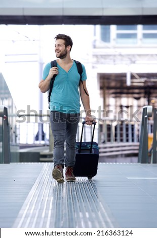 Full length portrait of a cheerful man walking with bags at train station