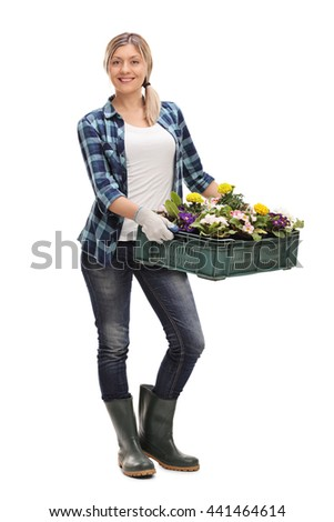 Full length portrait of a cheerful woman holding a rack of flowers isolated on white background - stock photo