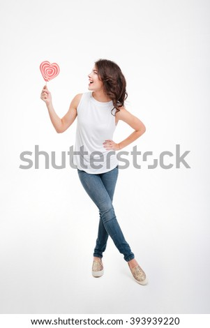 Full length portrait of a cheerful woman holding lollipop isolated on a white background - stock photo