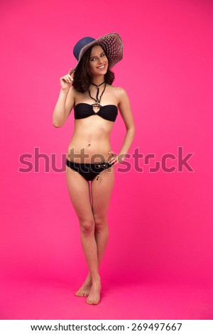 Full length portrait of a cheerful woman in swimsuit over pink background