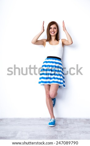Full length portrait of a cheerful woman posing at studio - stock photo