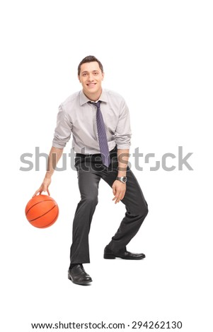Full length portrait of a cheerful young businessman playing basketball and looking at the camera isolated on white background - stock photo