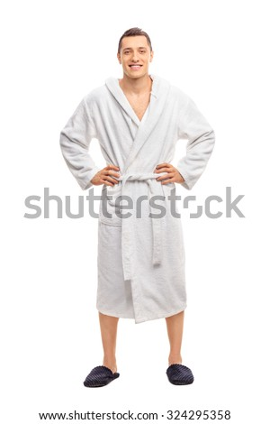 Full length portrait of a cheerful young man in a white bathrobe isolated on white background - stock photo