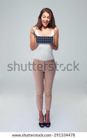 Full length portrait of a cheerful young woman opening gift box over gray background - stock photo