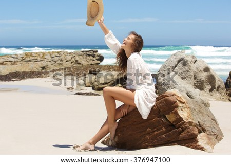 Full length portrait of a cheerful young woman with hat raised in the air at the beach  - stock photo