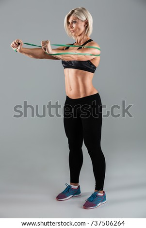 Full length portrait of a concentrated muscular adult sportswoman working out with a stretching band isolated over gray background