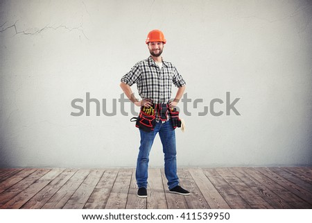 Full length portrait of a confident and smiling handyman in red helmet - stock photo