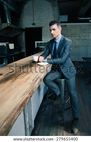 Full length portrait of a confident businessman in suit drinking coffee in cafe - stock photo