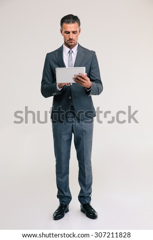Full length portrait of a confident businessman using tablet computer isolated on a white background - stock photo