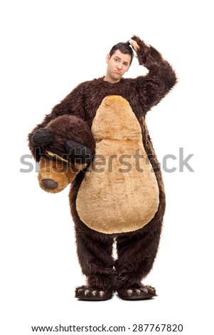 Full length portrait of a confused young man in a bear costume scratching his head and looking at the camera isolated on white background - stock photo