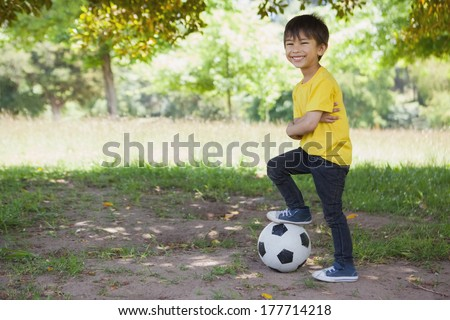 Full length portrait of a cute little boy with football standing at the park