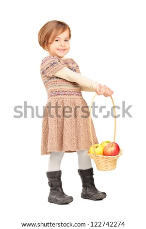 Full length portrait of a cute little girl holding a basket with apples isolated on white background