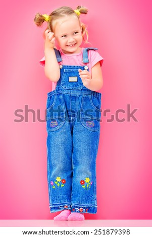 Full length portrait of a cute little girl over bright pink background. Happy childhood. - stock photo