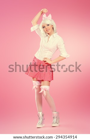 Full length portrait of a cute teen girl wearing white wig and school uniform with stockings posing over pink background. Anime style.  - stock photo