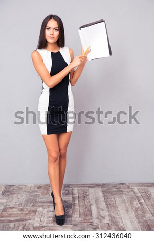 Full length portrait of a cute woman showing blank paper on gray background - stock photo