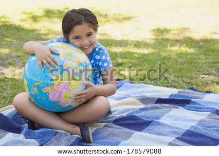 Full length portrait of a cute young girl holding globe at the park - stock photo