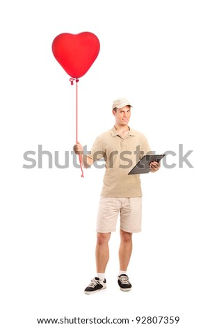 Full length portrait of a delivery boy delivering a red heart shaped balloon isolated on white background - stock photo