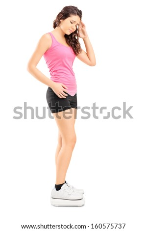 Full length portrait of a disappointed young female standing on weight scale isolated on white background