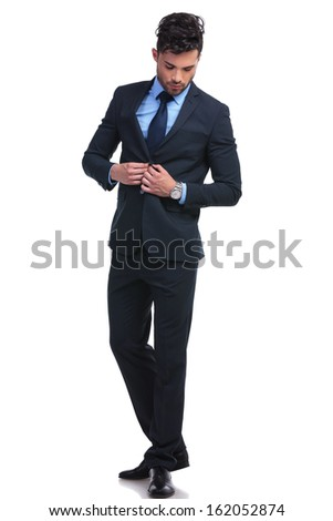 full length portrait of a fashion business man un buttoning his suit and looking down - stock photo