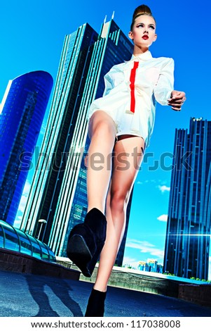Full length portrait of a fashion model walking down the street of a big city. - stock photo