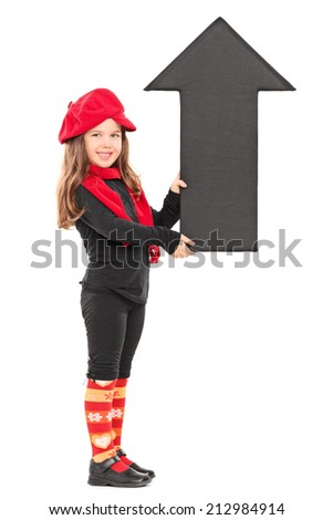 Full length portrait of a fashionable little girl holding a big arrow pointing up isolated on white background - stock photo