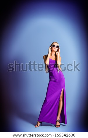 Full length portrait of a fashionable model in an evening dress and sunglasses. - stock photo