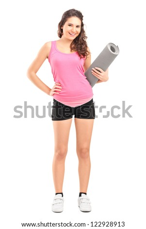 Full length portrait of a female athlete holding a mat isolated on white background