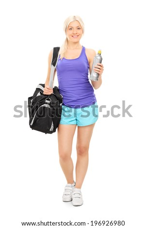 Full length portrait of a female athlete holding a water bottle and carrying a sports bag isolated on white background - stock photo