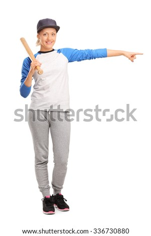 Full length portrait of a female baseball player holding a baseball bat and pointing right with her hand isolated on white background - stock photo